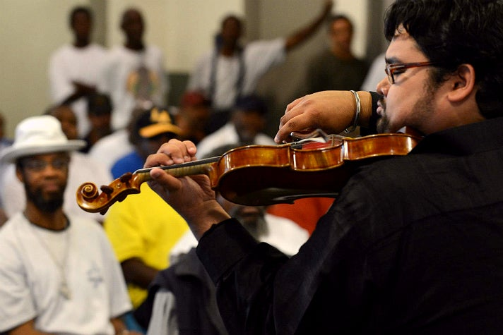 Street Symphony Artistic Director Vijay Gupta performing at the Midnight Mission